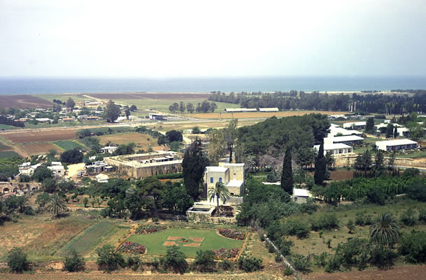An aerial photograph of the village of Mazra'ih showing the mansion where Bahá'u'lláh lived. The Mediterranean Sea is in the distance.